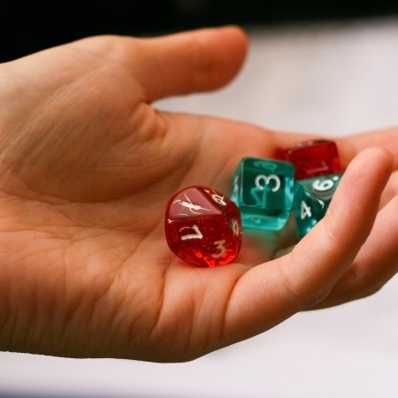a hand holding four dice